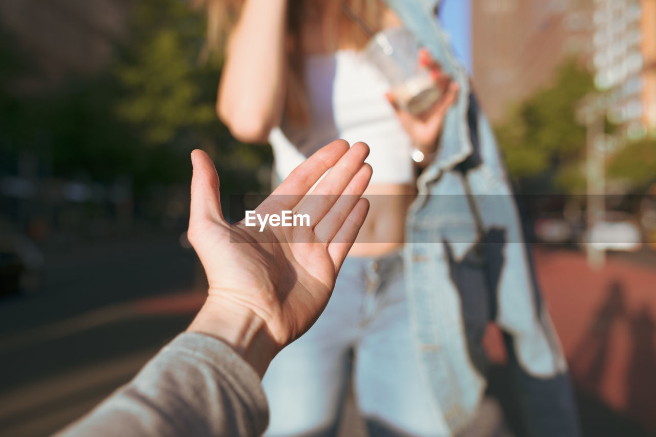 Cropped hand gesturing towards woman standing on footpath in city during sunny day