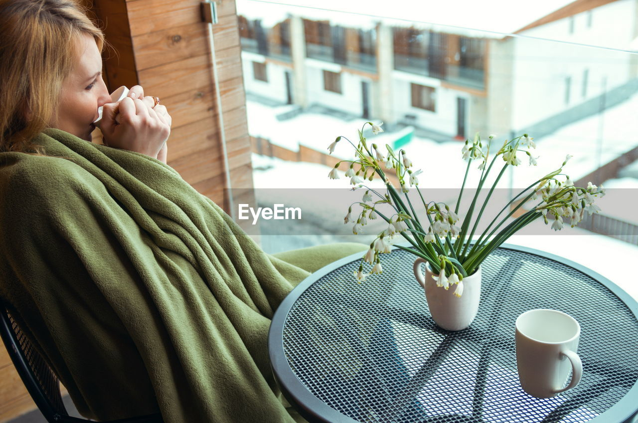Woman drinking coffee while sitting in balcony at home