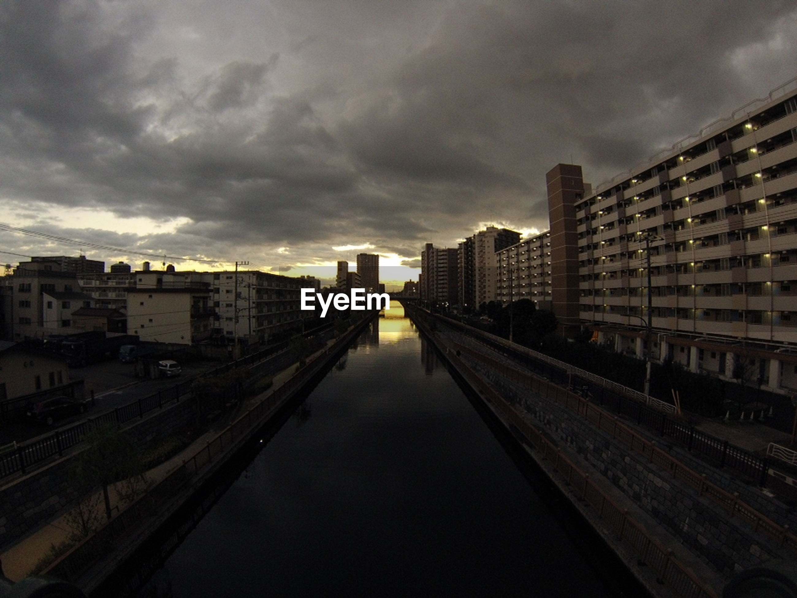 architecture, built structure, building exterior, sky, cloud - sky, city, water, cloudy, transportation, canal, diminishing perspective, weather, river, the way forward, dusk, overcast, cloud, high angle view, bridge - man made structure, building