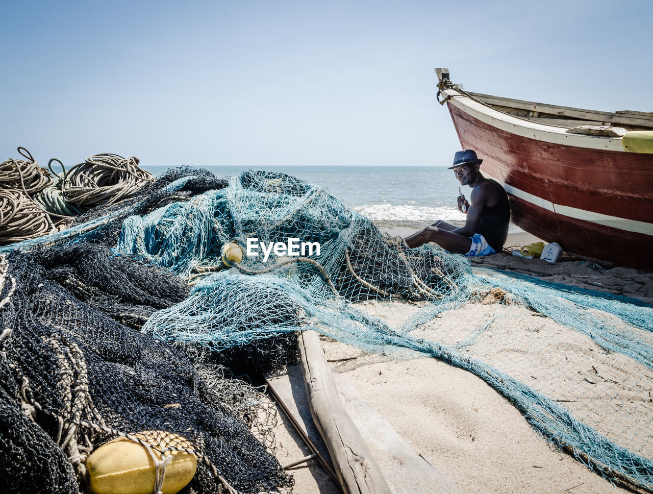 nautical vessel, water, mode of transportation, sea, transportation, fishing net, sky, fishing industry, rope, nature, commercial fishing net, fishing, day, beach, moored, clear sky, no people, horizon, land, outdoors, horizon over water, fishing boat