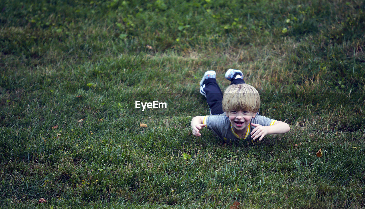 Boy Playing On Grass