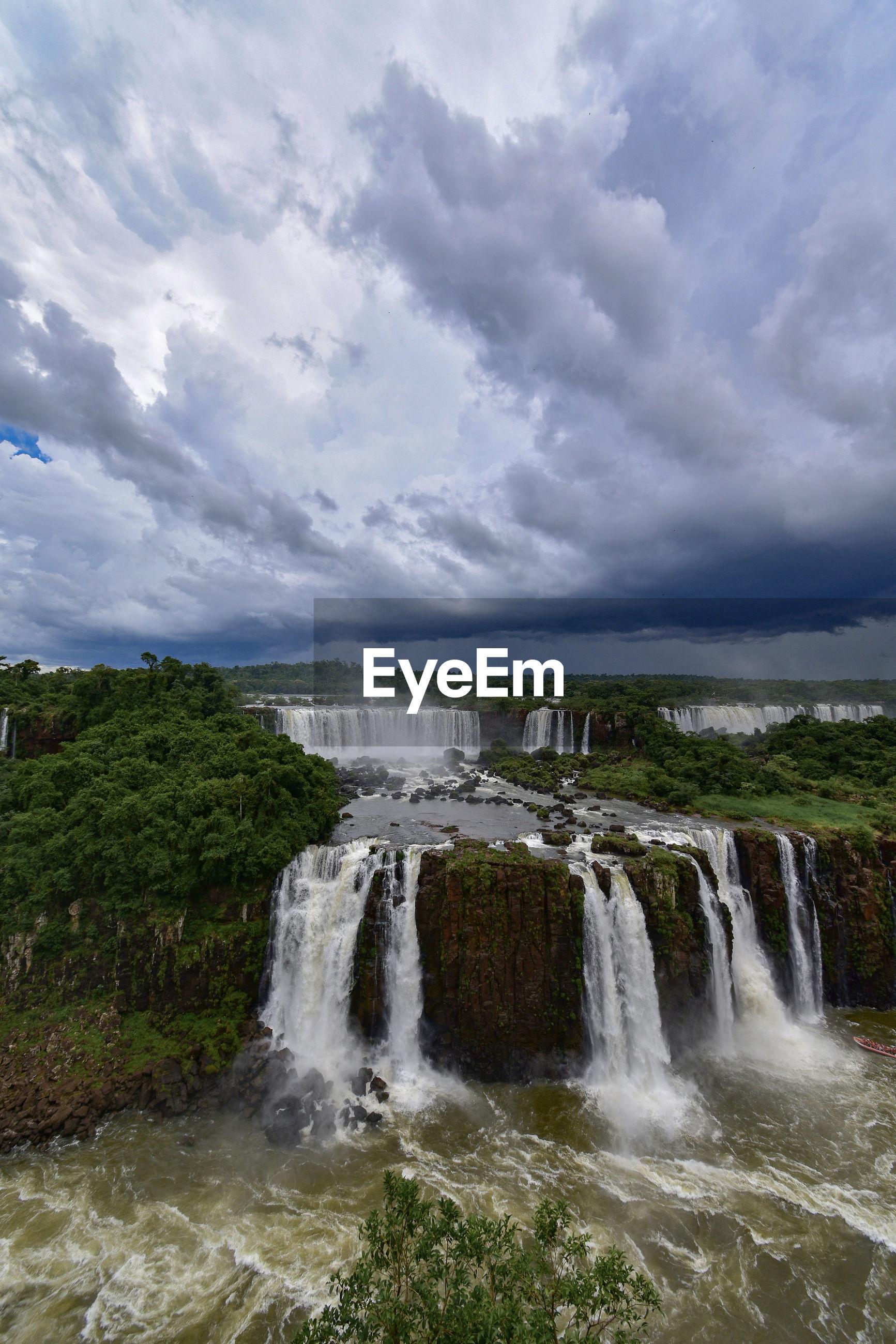 Scenic view of waterfall against sky - cataratas do iguaçu