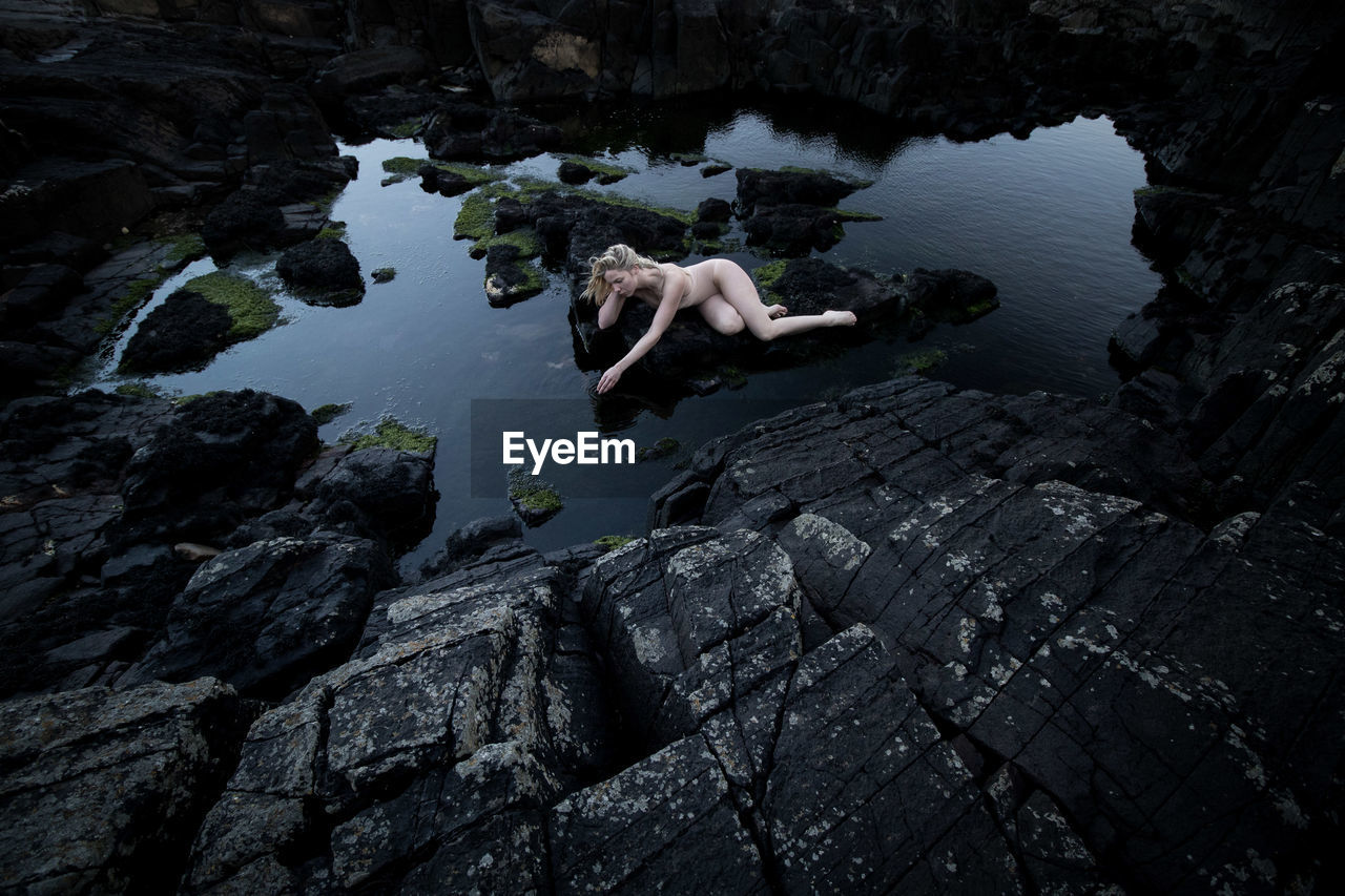 Naked woman on rock by lake against sky