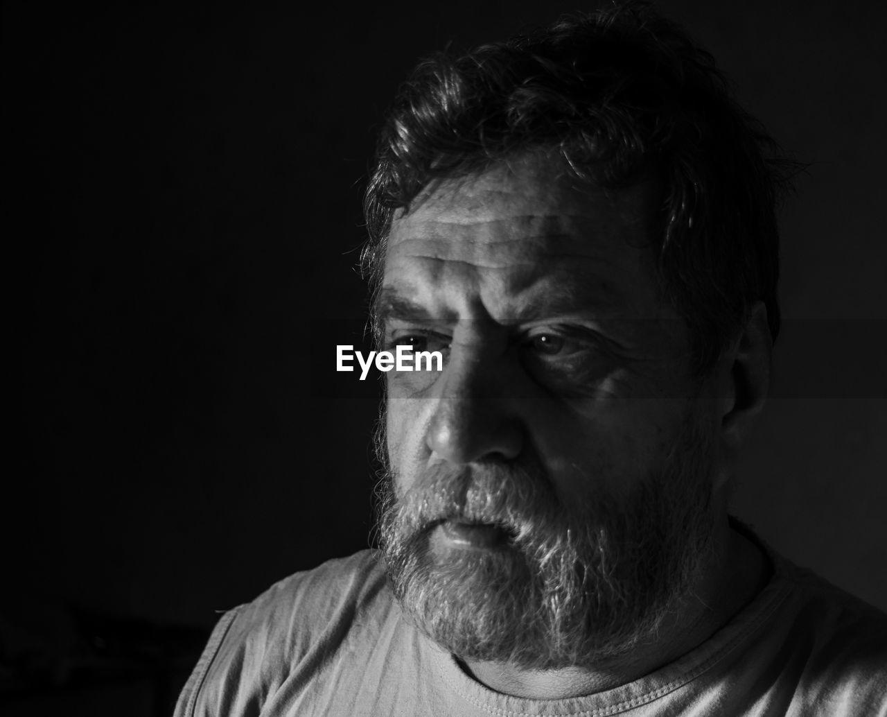 Close-Up Of Portrait Of Man Against Black Background
