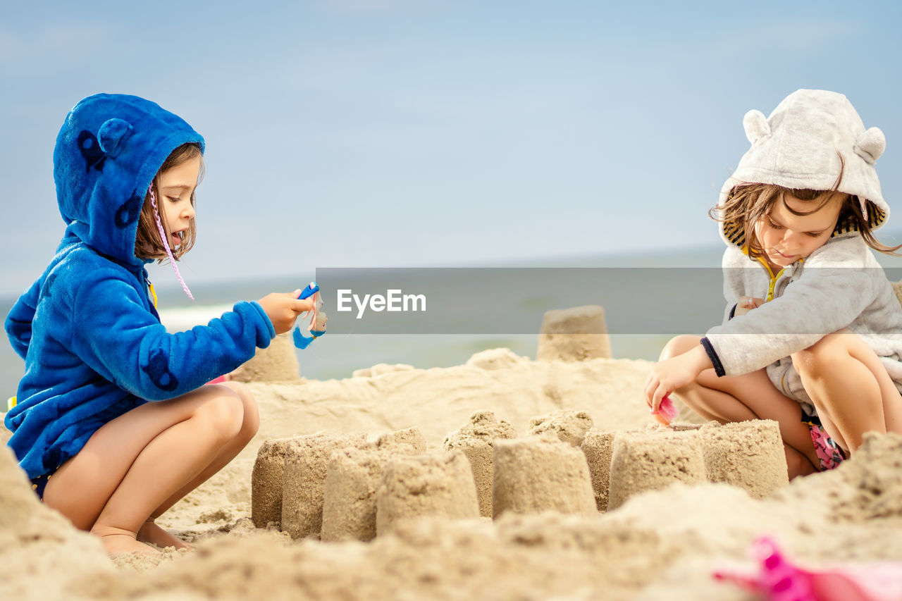 Siblings making sandcastle while crouching at beach