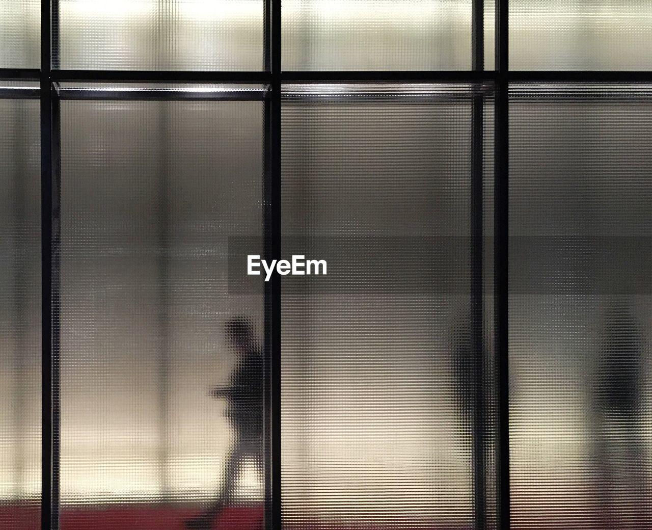 People Seen Through Translucent Glass