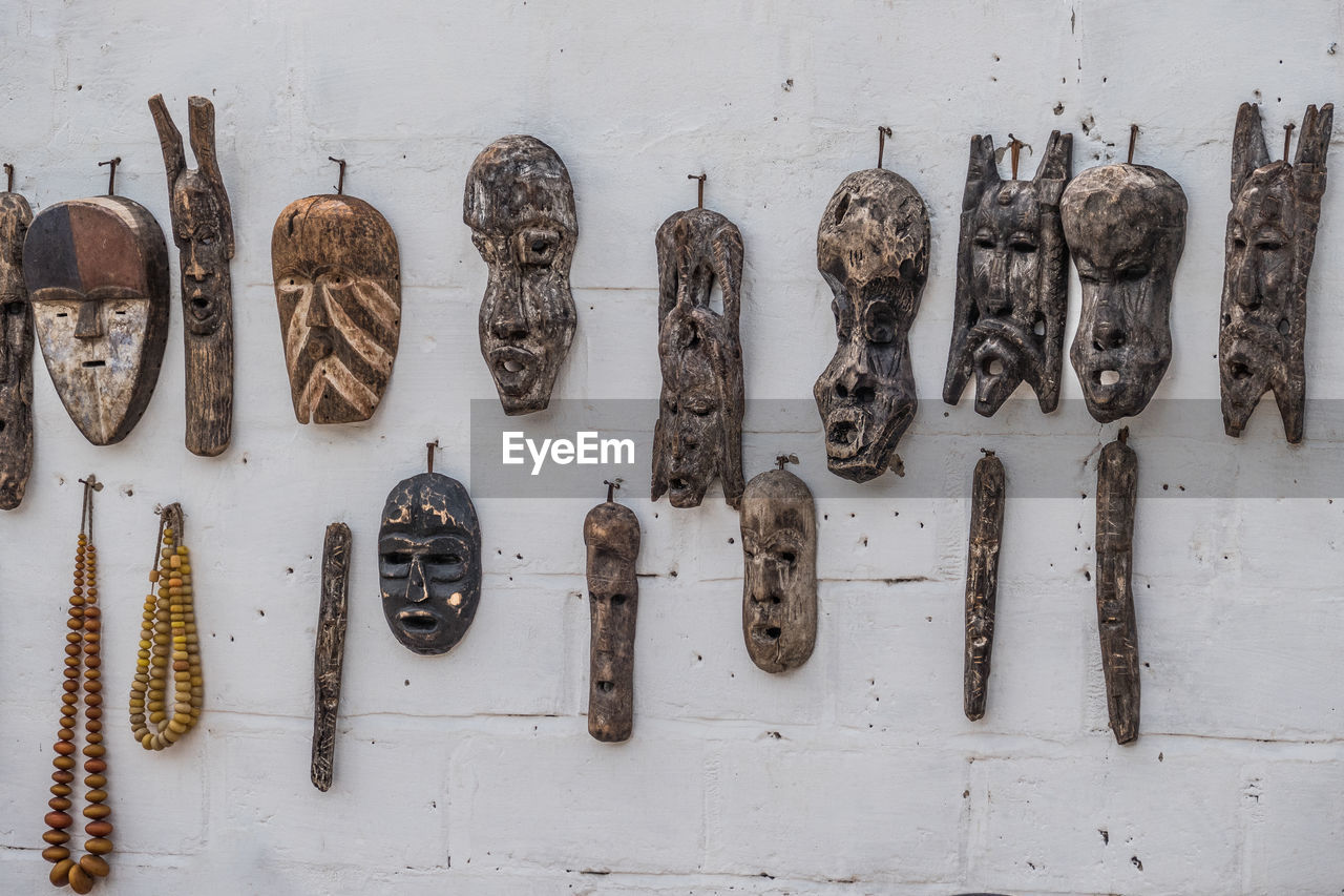 wall - building feature, side by side, no people, indoors, work tool, representation, metal, human representation, creativity, variation, old, wood - material, choice, arrangement, hanging, art and craft, rusty, still life, brown, group of objects