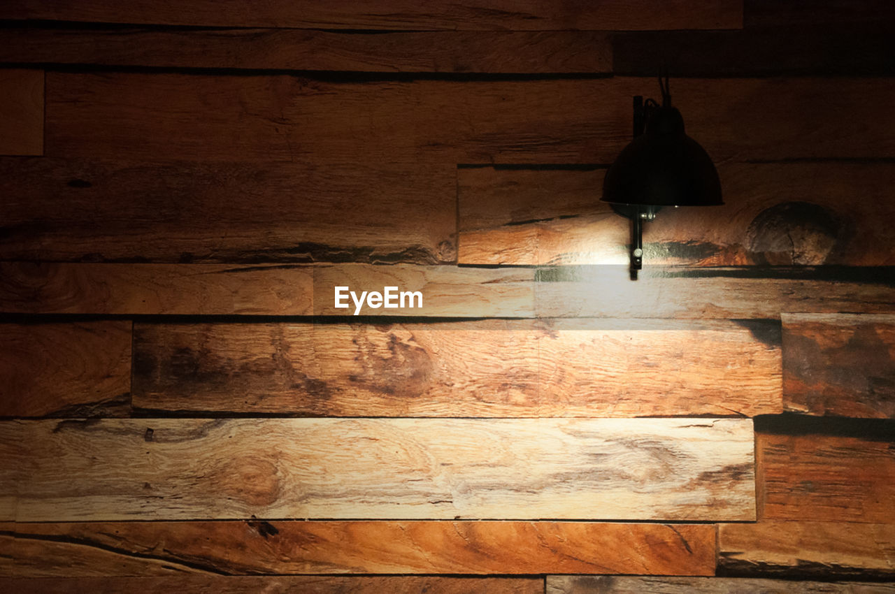 wood - material, indoors, wall - building feature, wood, real people, architecture, low section, flooring, hanging, illuminated, lighting equipment, built structure, night, dark, hardwood floor, pattern