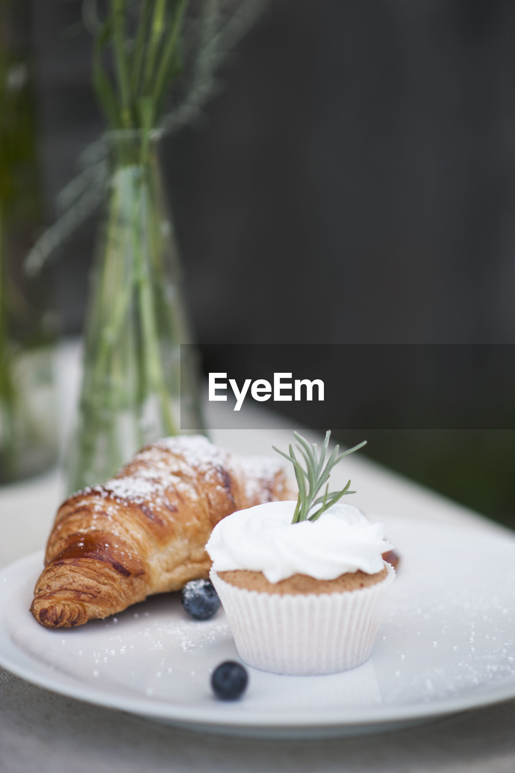 Close-up of cupcake with croissant on plate