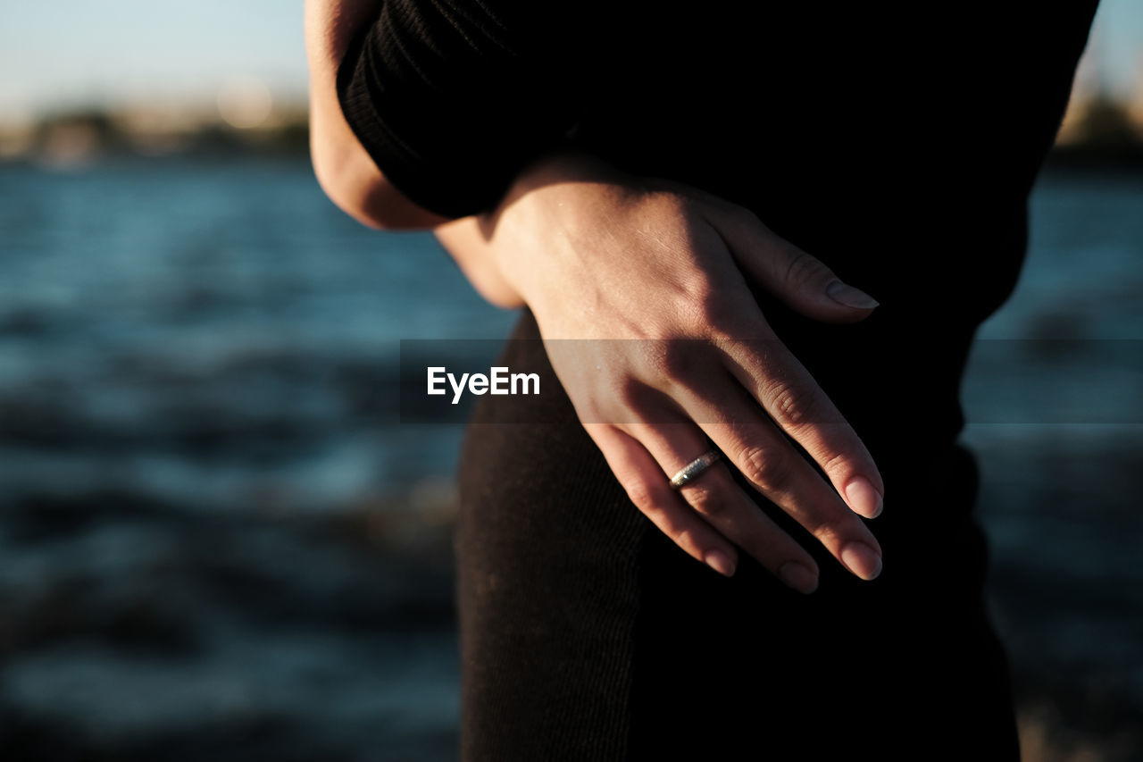 Midsection Of Woman Wearing Ring While Standing At Beach