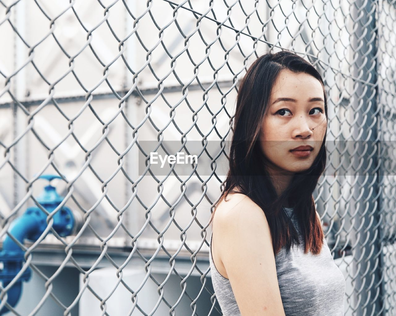 Thoughtful Woman Standing Against Chainlink Fence