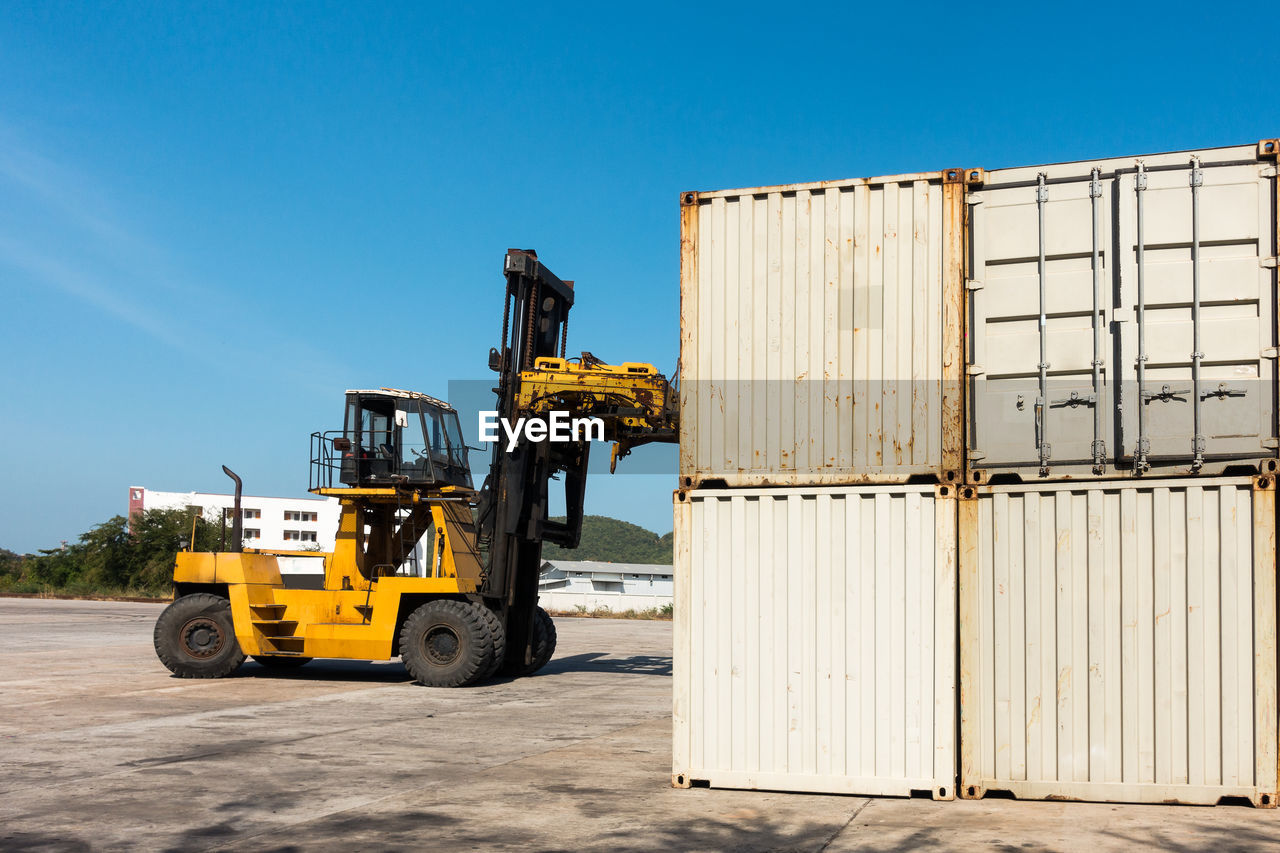 Cargo containers at dock against blue sky
