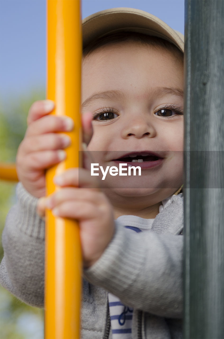 Close-up portrait of cheerful baby boy holding yellow pole