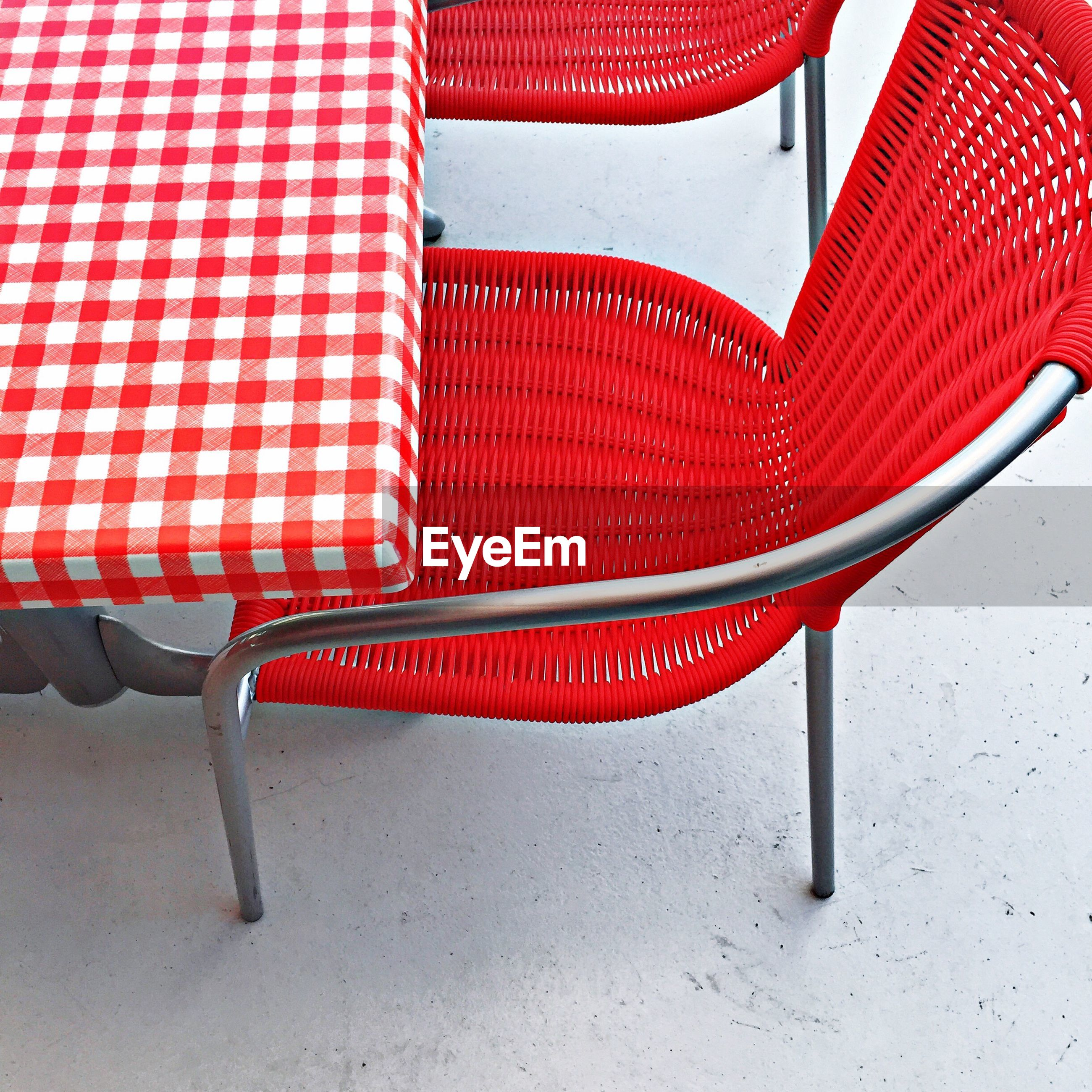 High angle view of empty red chair by table at cafe