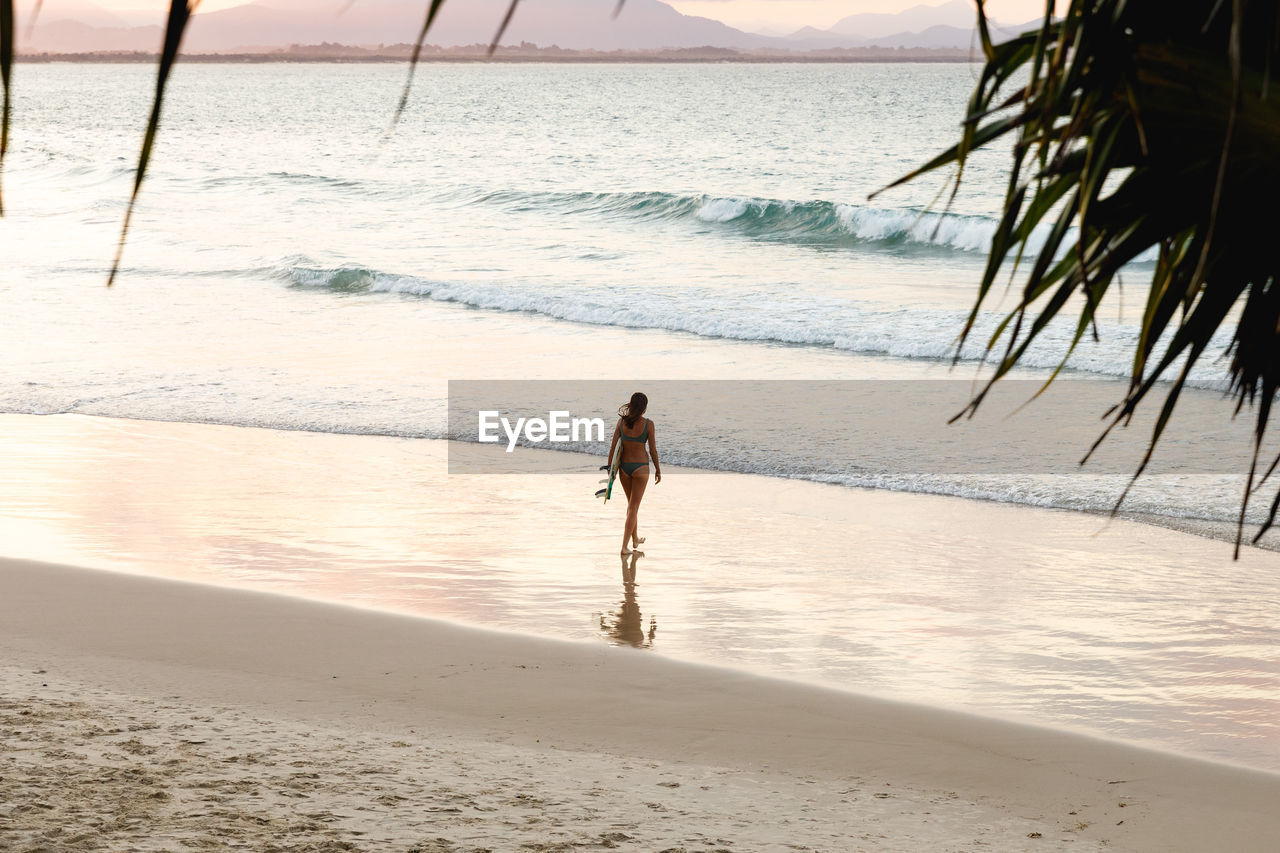 Rear view of woman in bikini with surfboard walking at beach during sunset