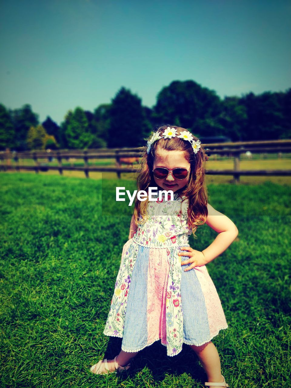 Full length portrait of cute fashionable girl wearing sunglasses and dress standing on grassy field during sunny day