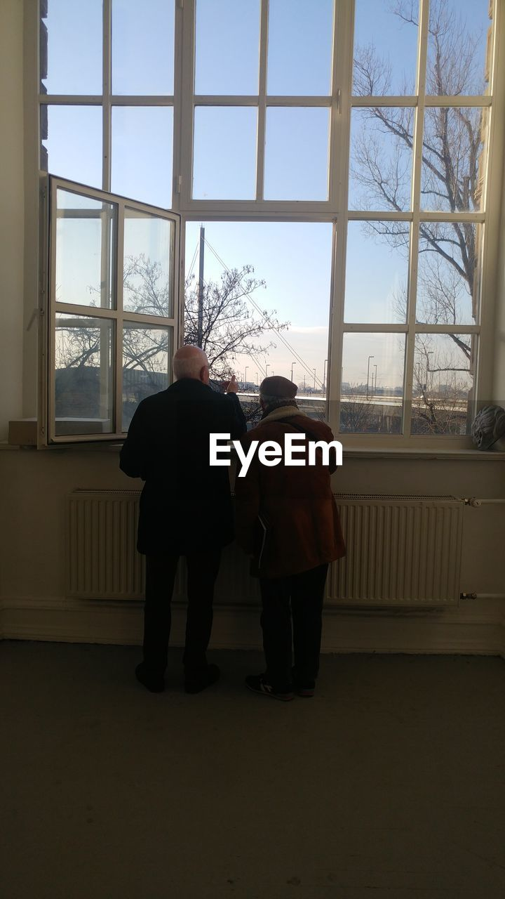 window, rear view, togetherness, indoors, full length, senior adult, real people, two people, senior women, standing, winter, men, day, senior men, looking through window, snow, lifestyles, built structure, women, friendship, cold temperature, architecture, warm clothing, sky, adult, people