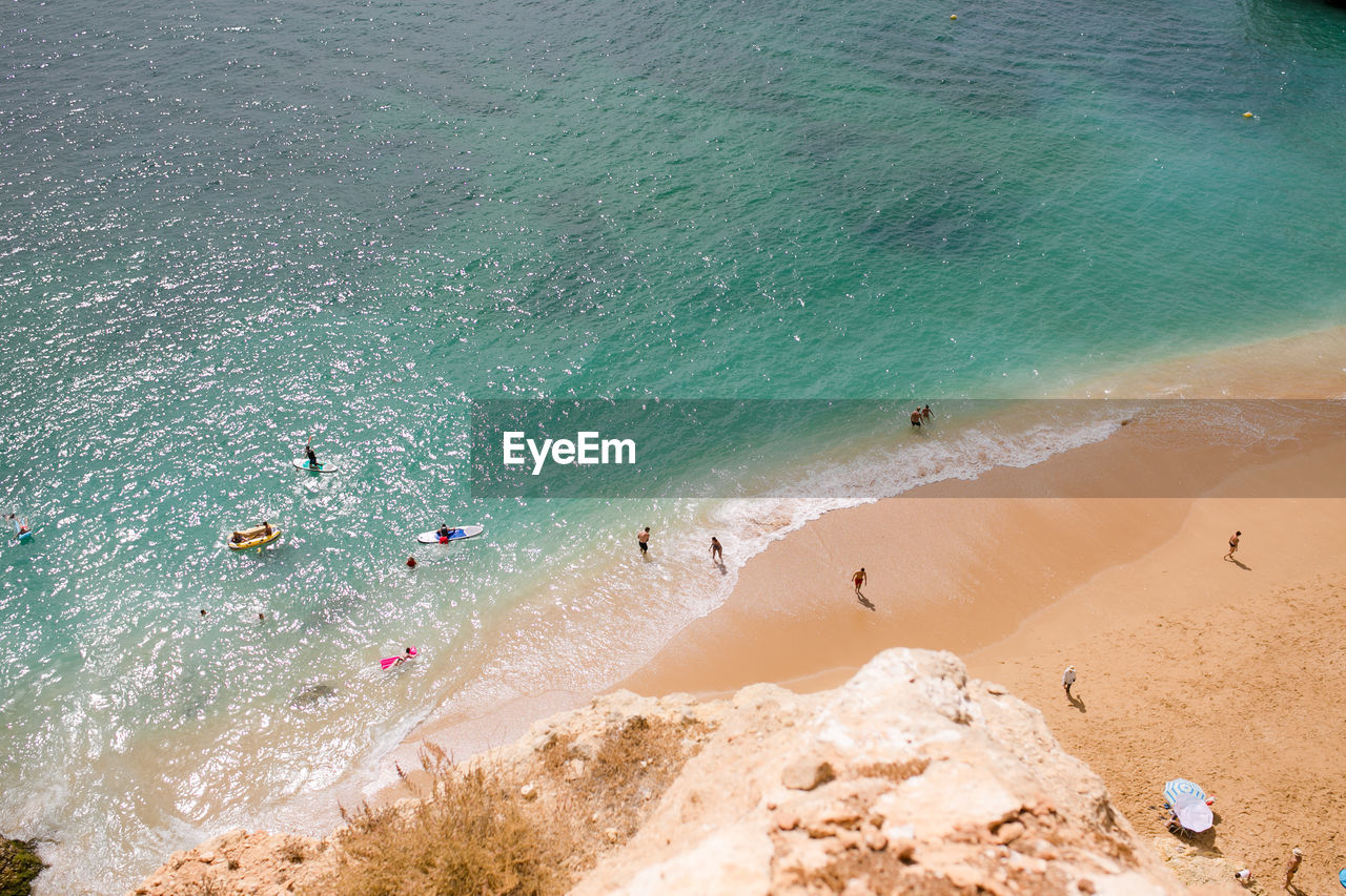 sea, water, beach, land, beauty in nature, high angle view, sand, scenics - nature, nature, group of people, day, tranquility, tranquil scene, real people, motion, rock, wave, outdoors, incidental people, turquoise colored