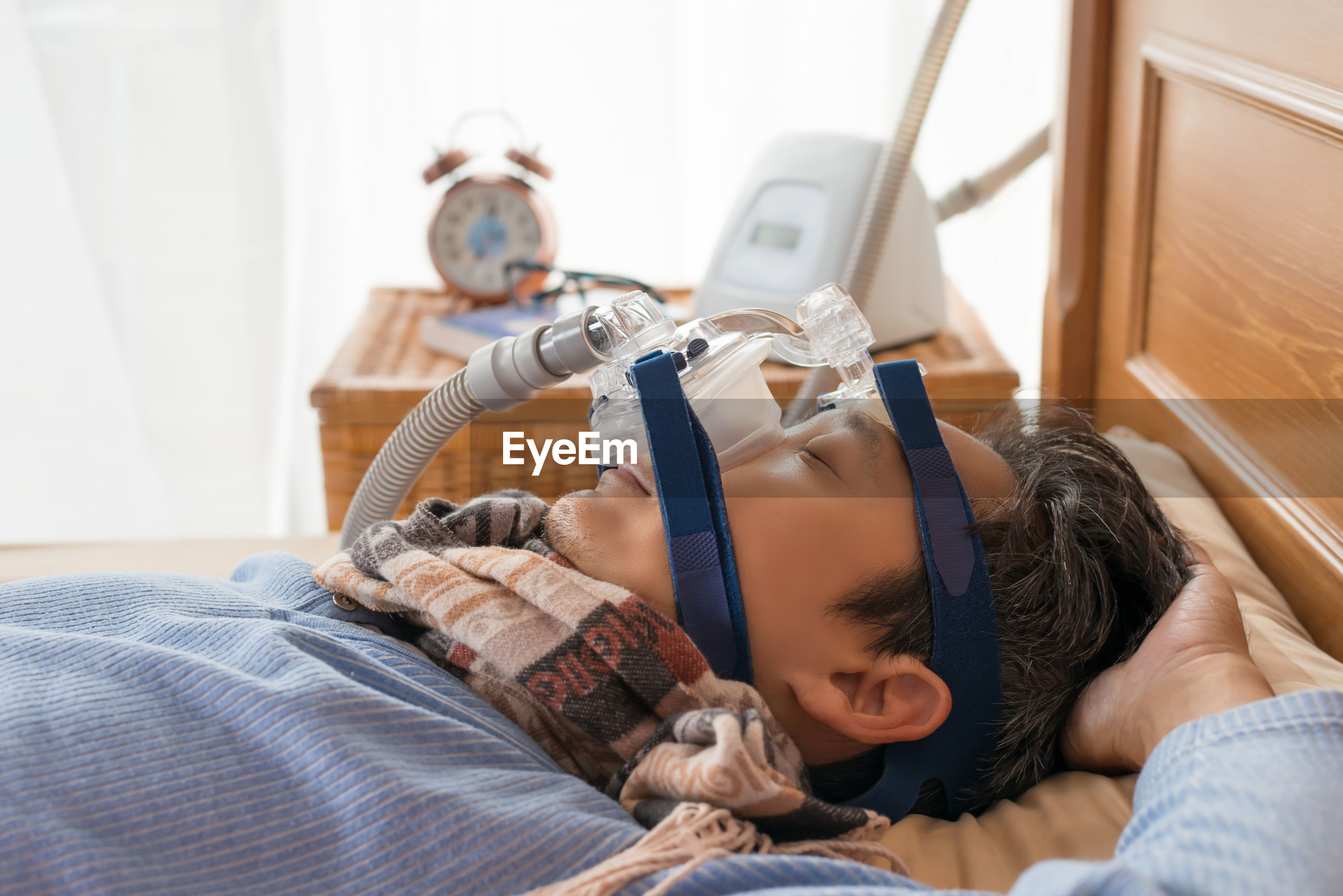 Mature man wearing oxygen mask while sleeping on bed