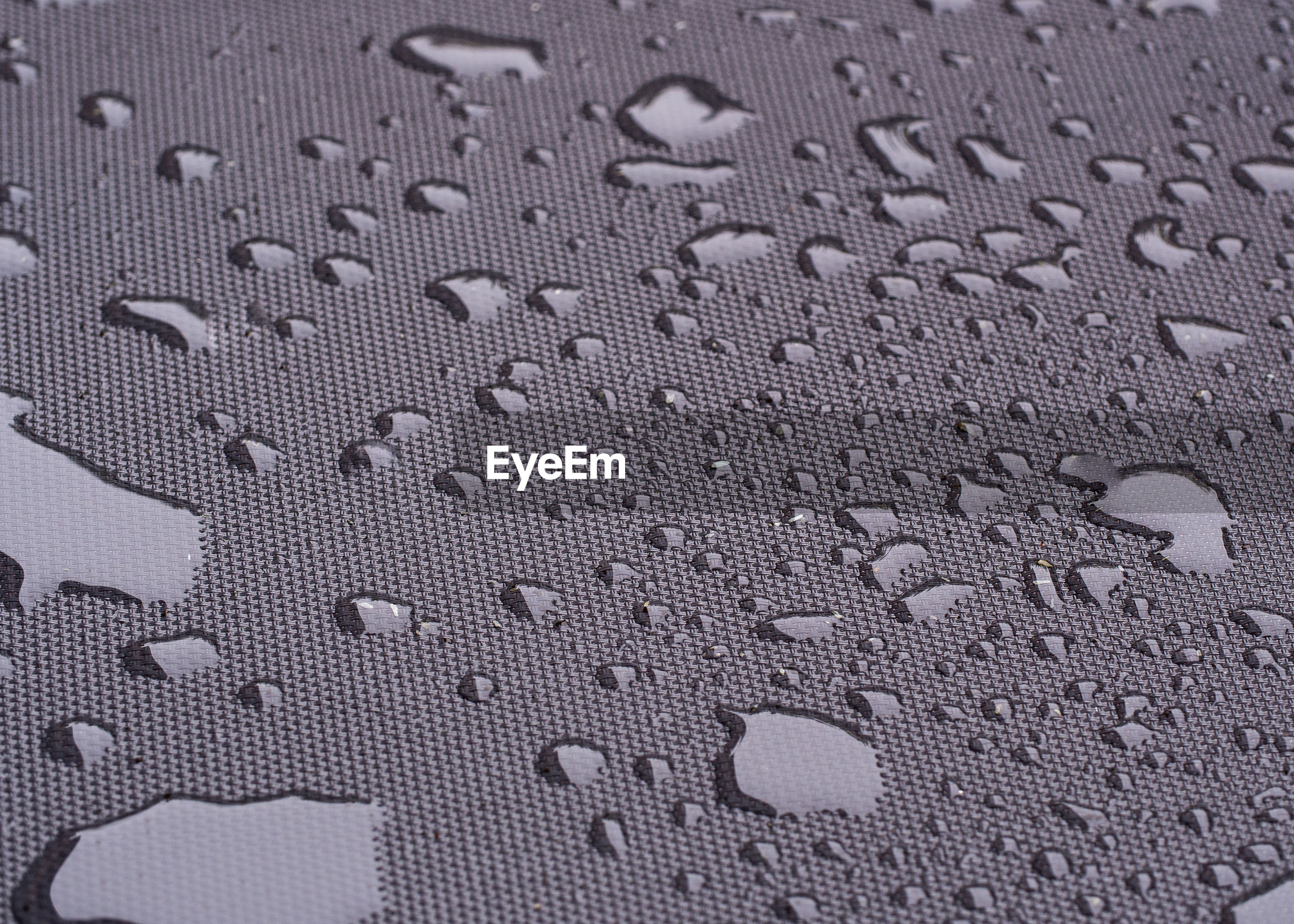 FULL FRAME SHOT OF WATER DROPS ON TEXTURED SURFACE