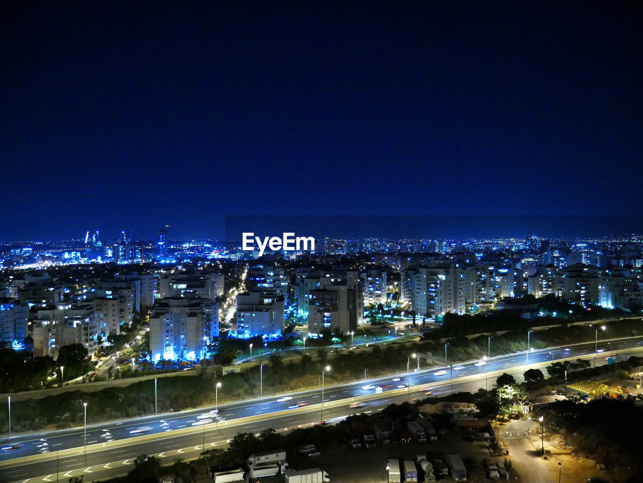 illuminated, city, night, building exterior, architecture, built structure, sky, cityscape, road, copy space, high angle view, street, no people, city life, blue, nature, transportation, motion, building, outdoors, office building exterior, skyscraper