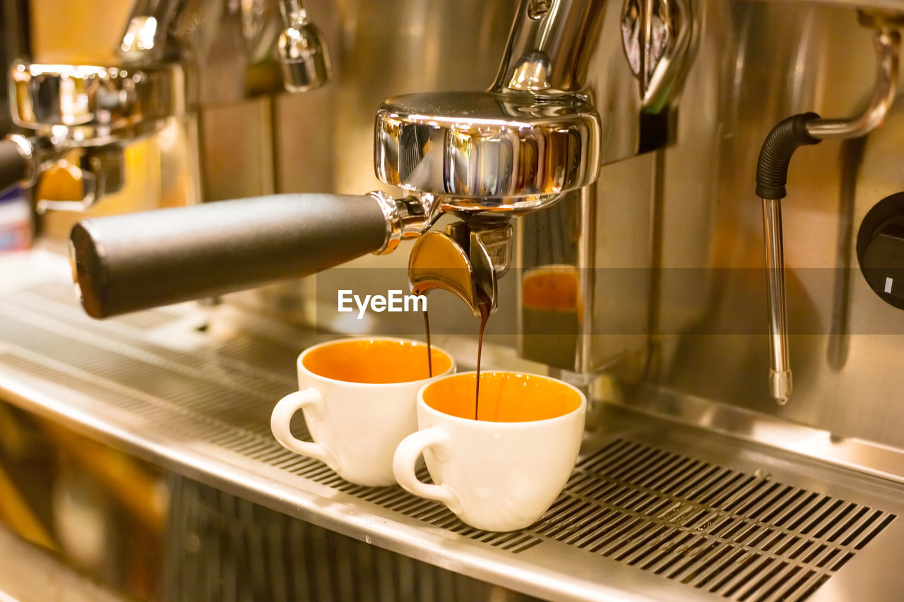 food and drink, cup, mug, drink, coffee maker, coffee, pouring, refreshment, coffee cup, appliance, espresso maker, coffee - drink, indoors, machinery, motion, preparation, cafe, close-up, no people, coffee shop, tea cup, flowing