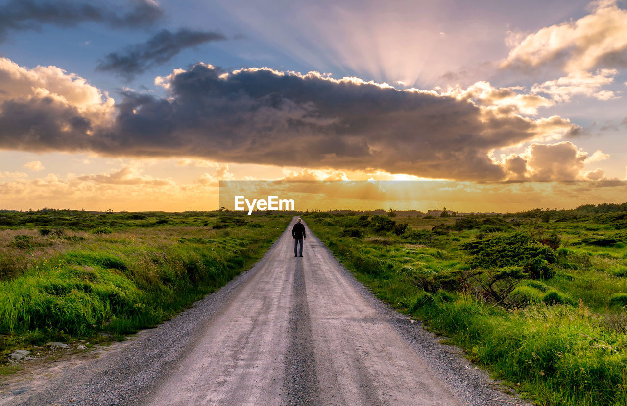 Man standing on road passing through landscape against cloudy sky