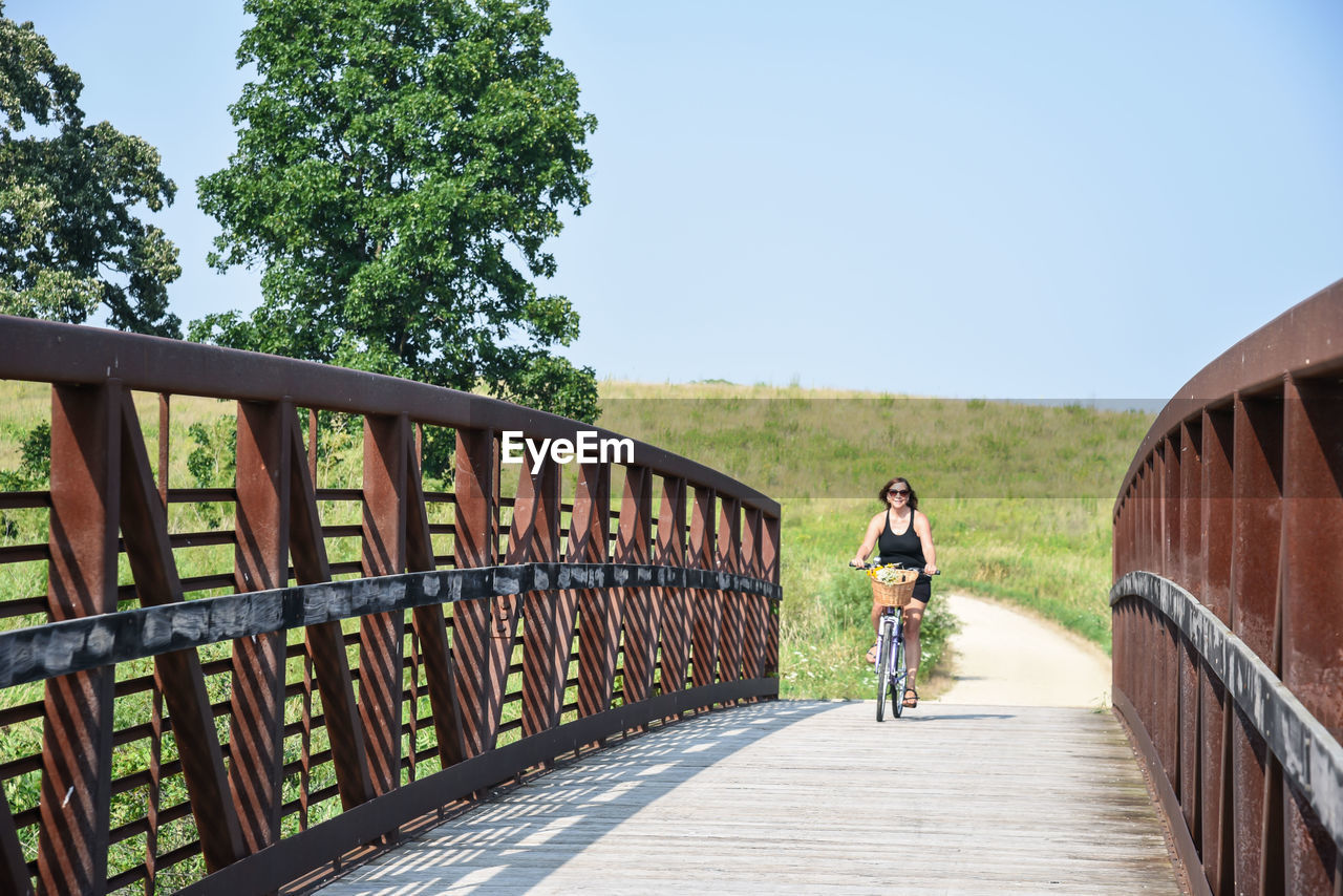 Mature woman riding bicycle on footbridge against clear sky