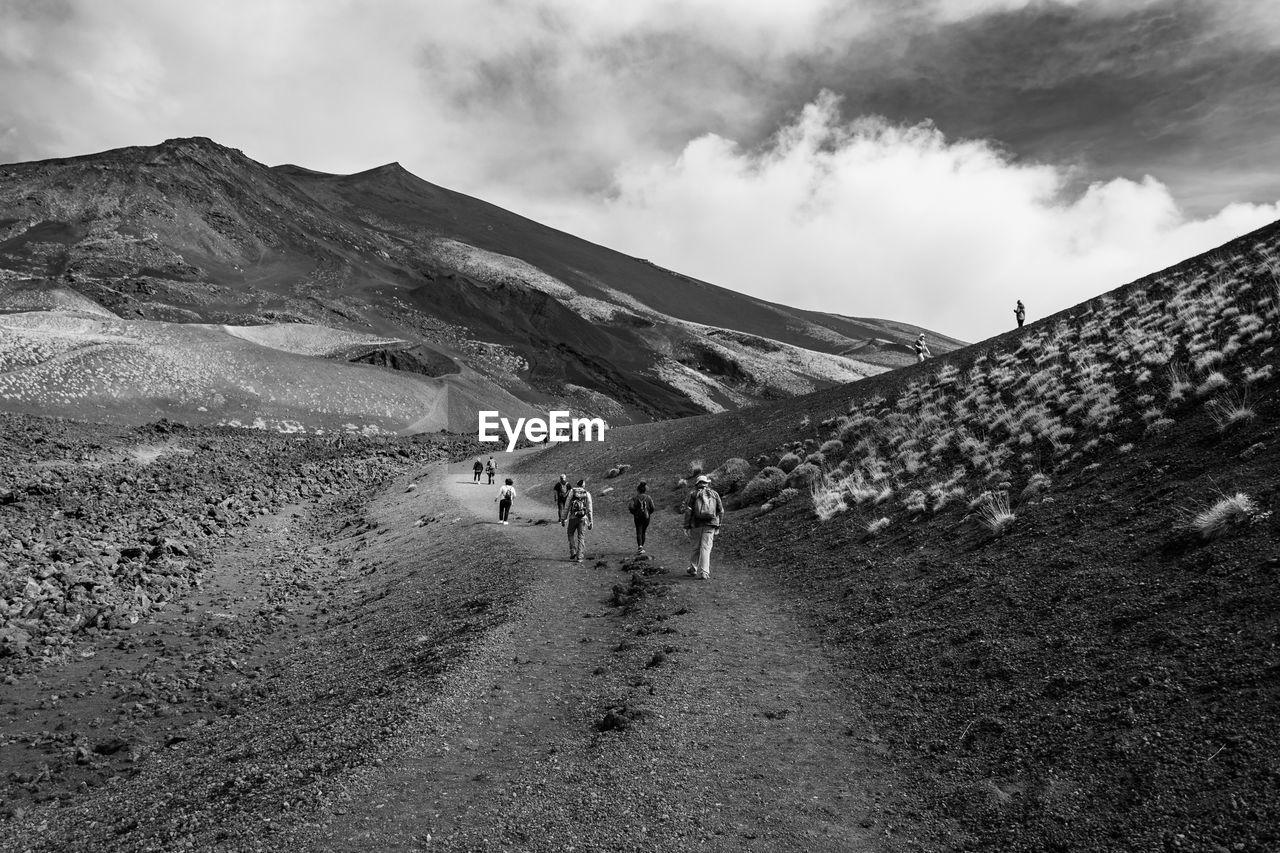 People Walking On Mountain Against Sky
