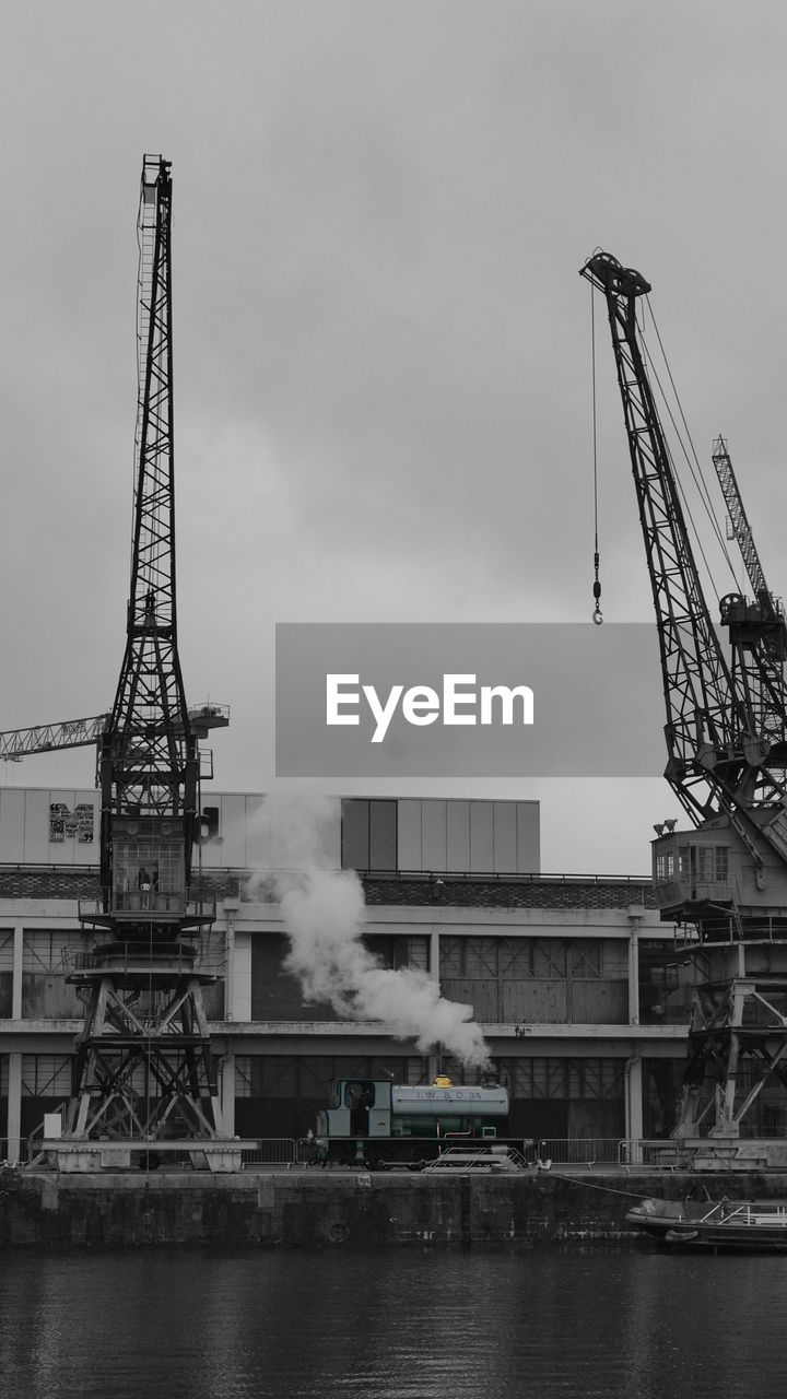 industry, machinery, architecture, sky, water, crane - construction machinery, built structure, no people, day, nature, building exterior, factory, smoke - physical structure, environmental issues, outdoors, transportation, development, construction industry, waterfront, pollution, air pollution, industrial equipment