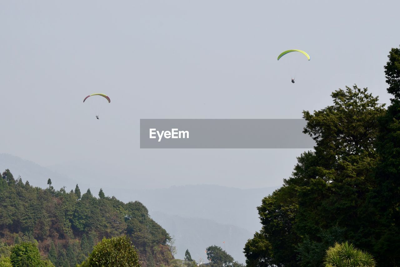 Low angle view of people paragliding against sky