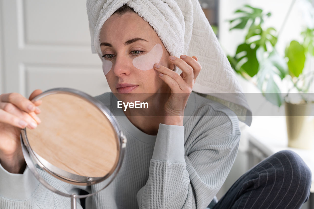 Woman applying medical eye patches
