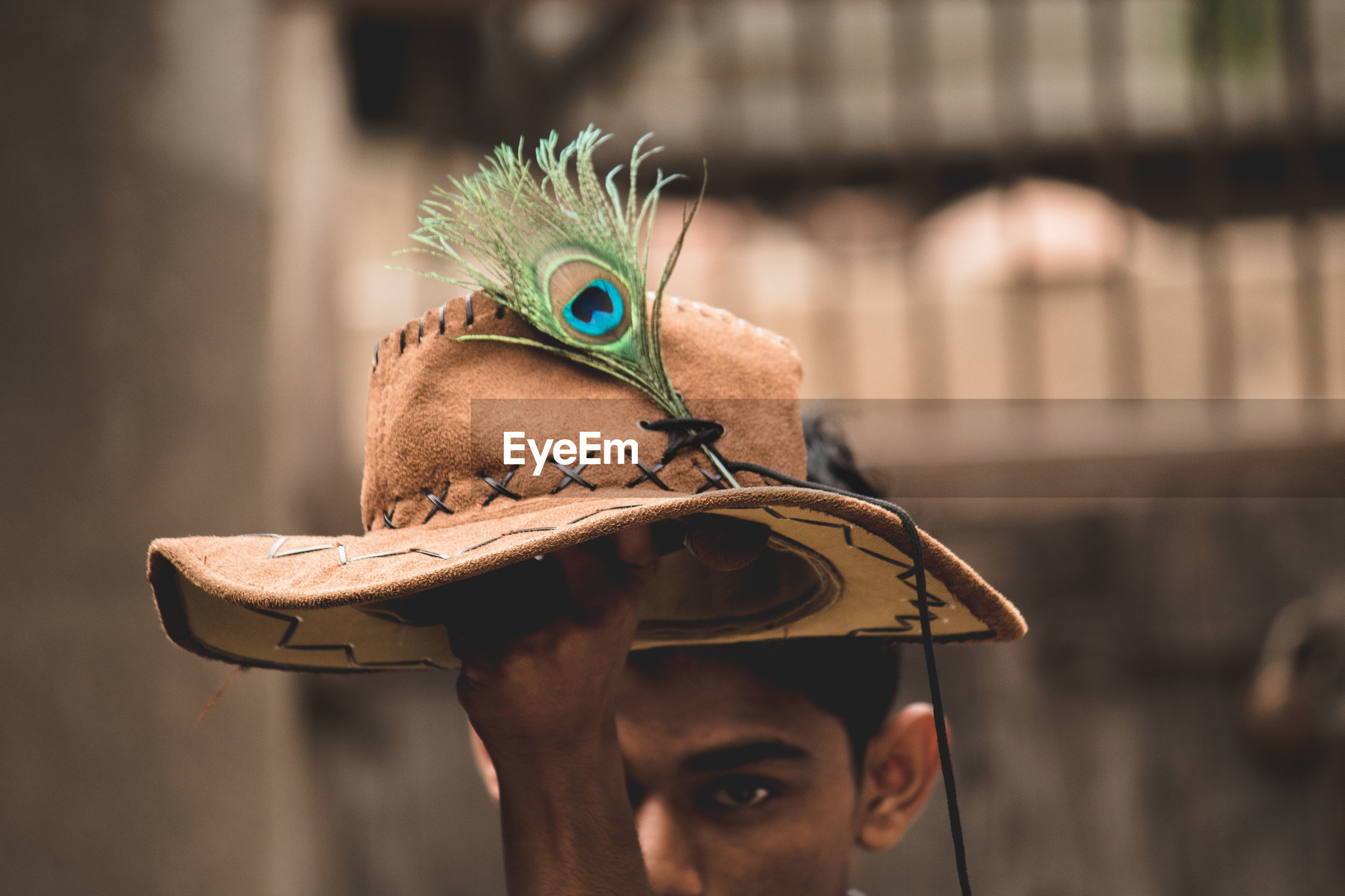 Close-up of teenage boy holding hat and peacock feather while standing against wall