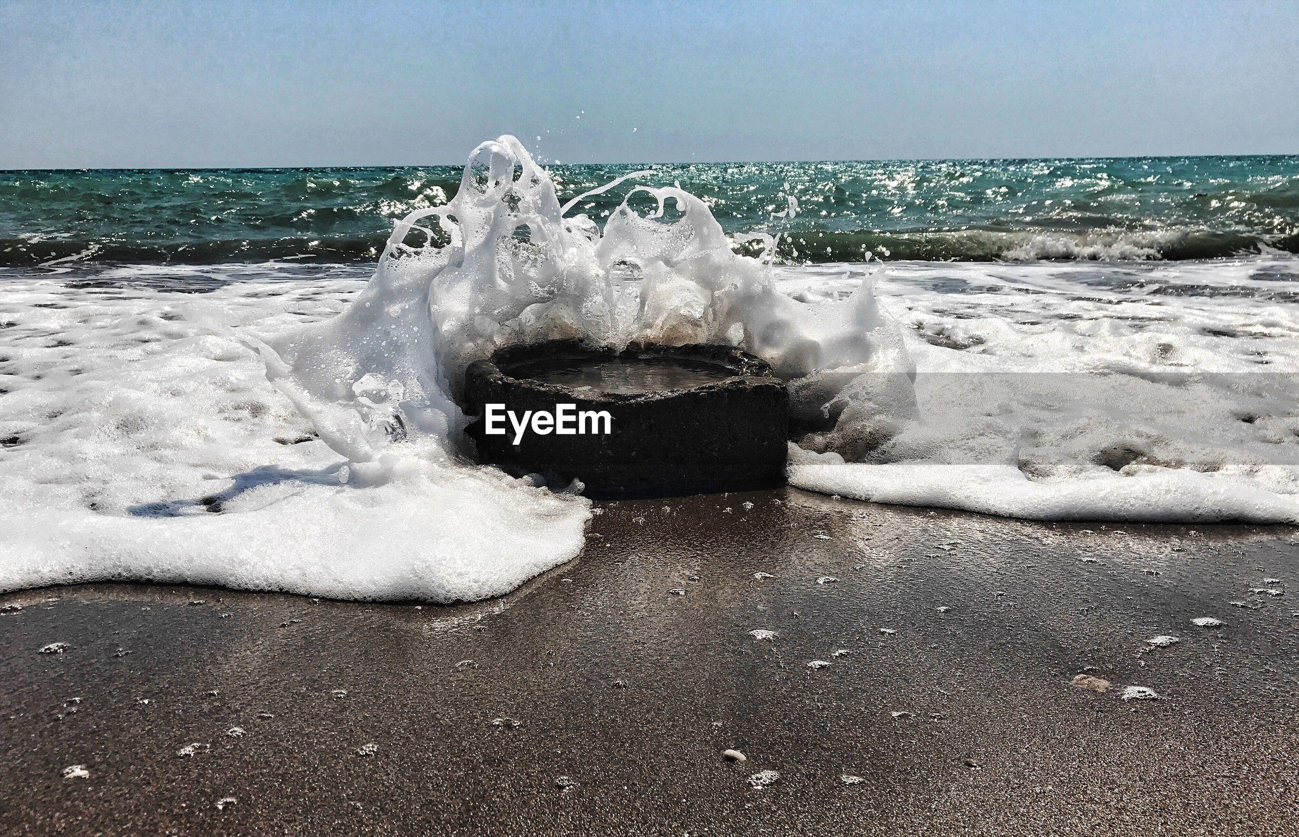 WAVES BREAKING ON BEACH AGAINST CLEAR SKY