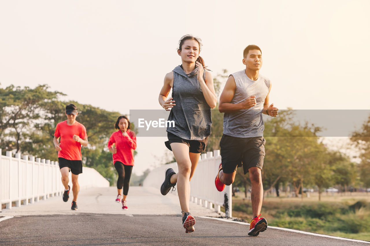 lifestyles, running, real people, sport, group of people, healthy lifestyle, women, exercising, leisure activity, motion, clothing, day, front view, men, vitality, nature, males, jogging, outdoors, effort, shorts