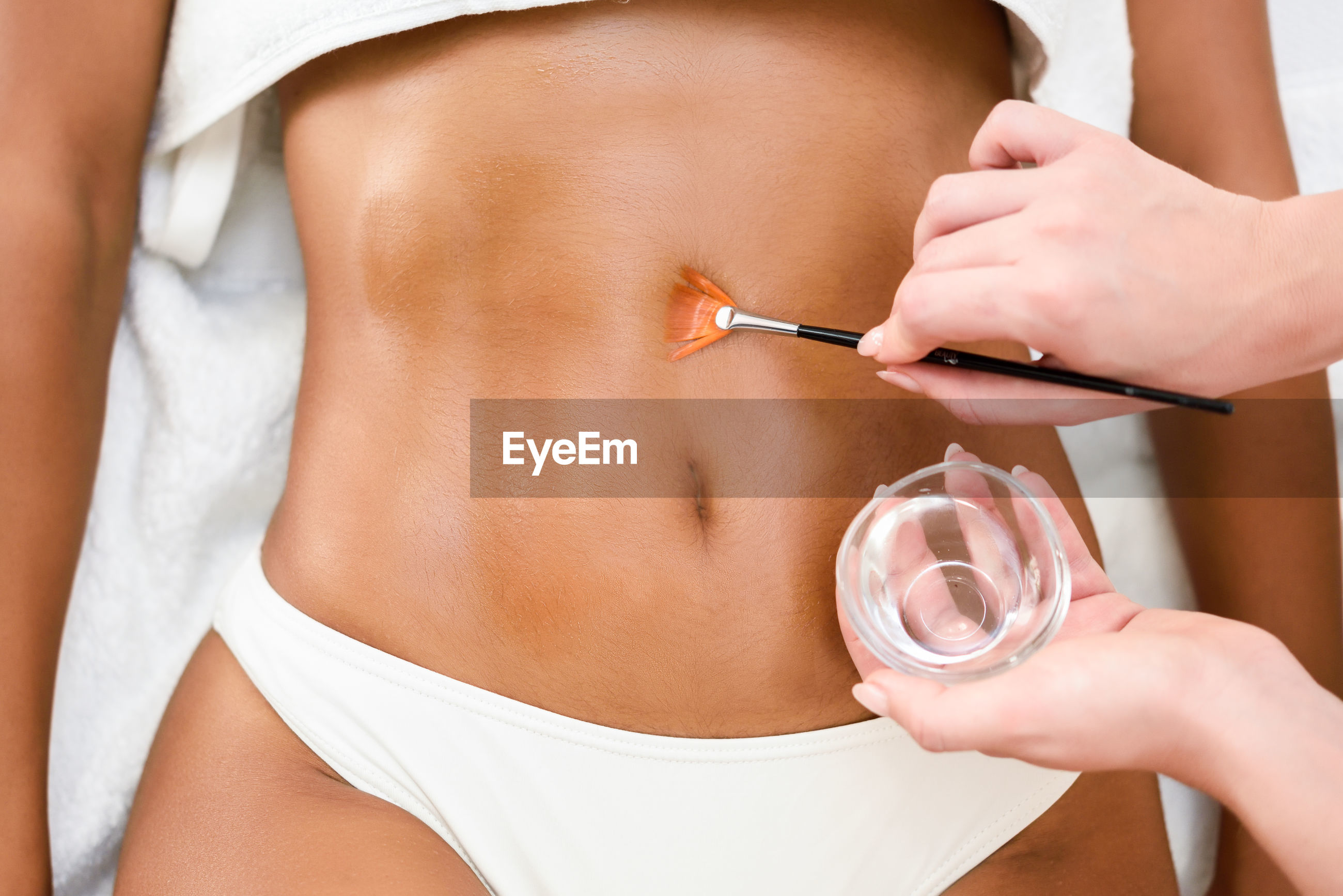 Cropped hands applying oil to midsection of woman