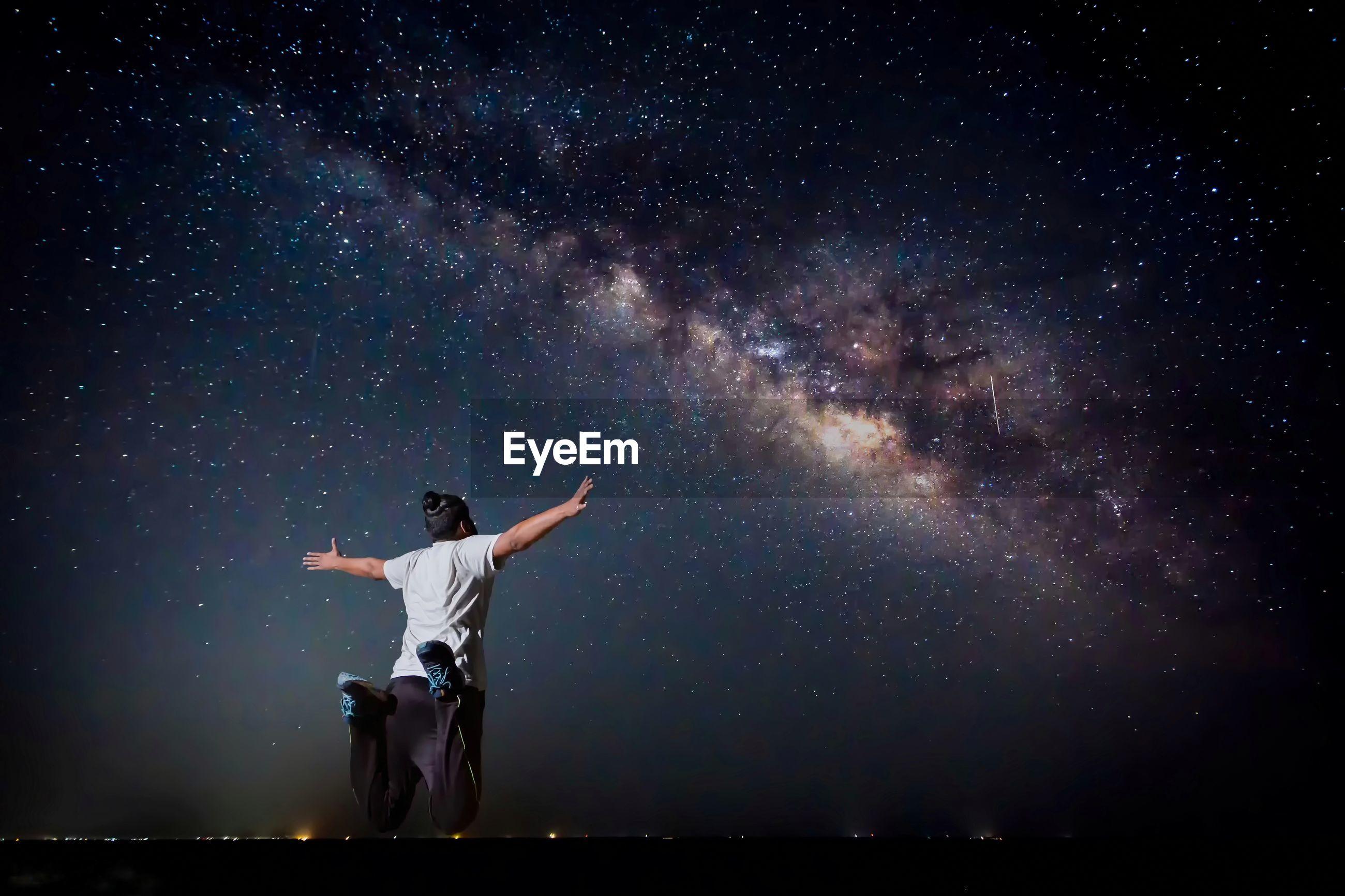 Full length of man jumping against star field at night