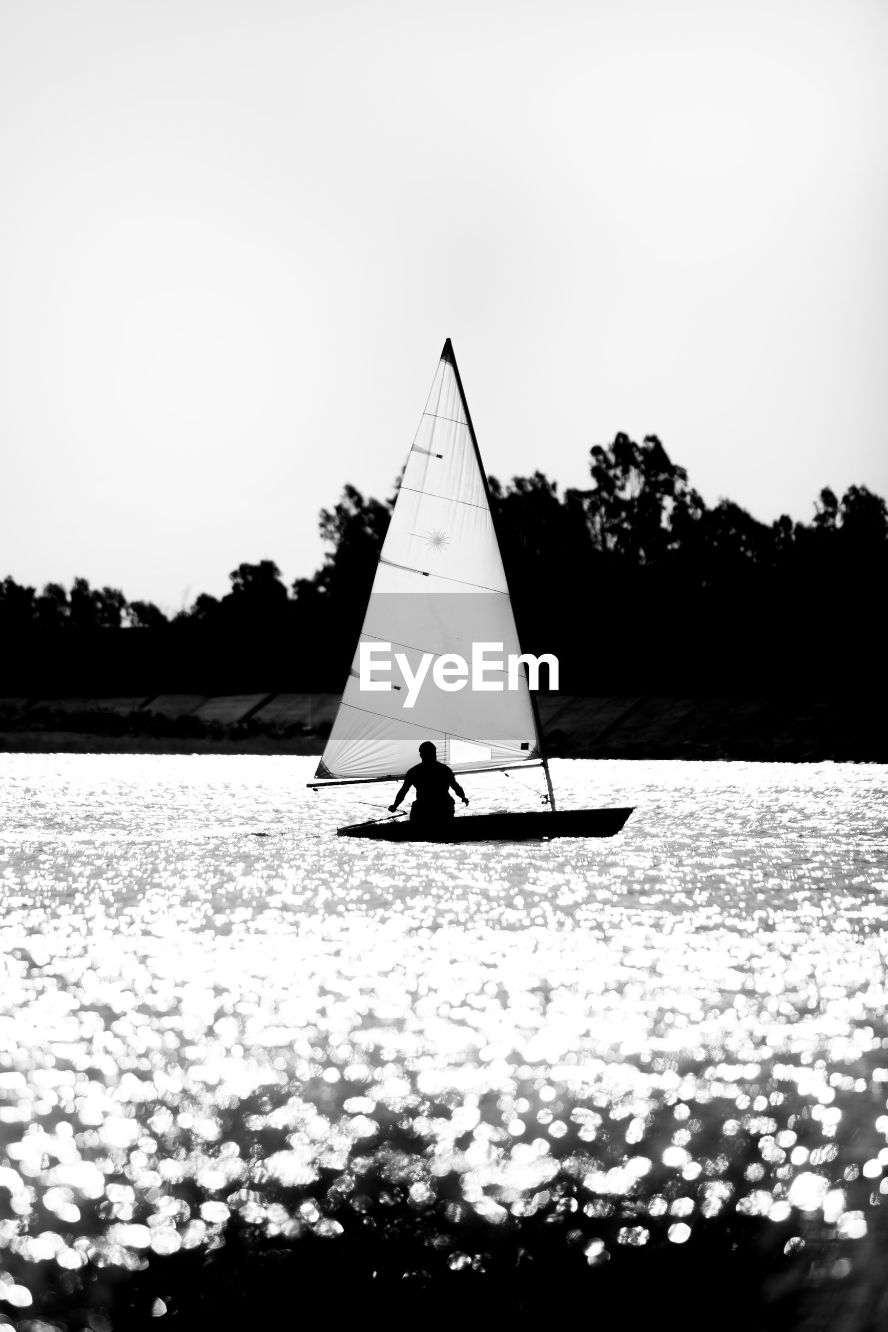 Man in sailboat on lake against clear sky
