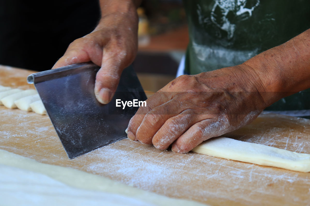 preparation, food, human hand, one person, preparing food, food and drink, real people, hand, occupation, indoors, dough, freshness, flour, table, human body part, making, skill, midsection, men, kneading, chef