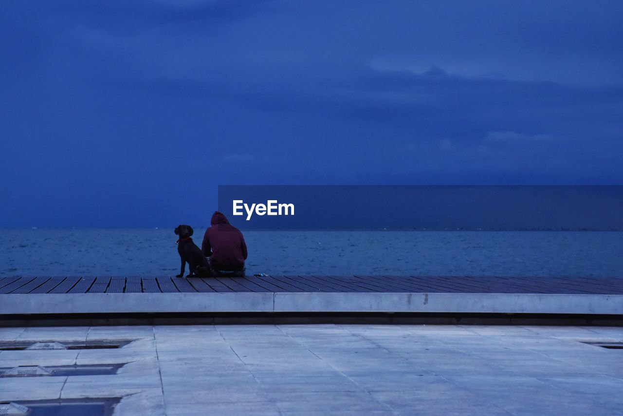 water, sky, two people, sea, real people, nature, leisure activity, rear view, lifestyles, men, adult, women, togetherness, sitting, people, horizon over water, beauty in nature, horizon, outdoors, couple - relationship, swimming pool, promenade