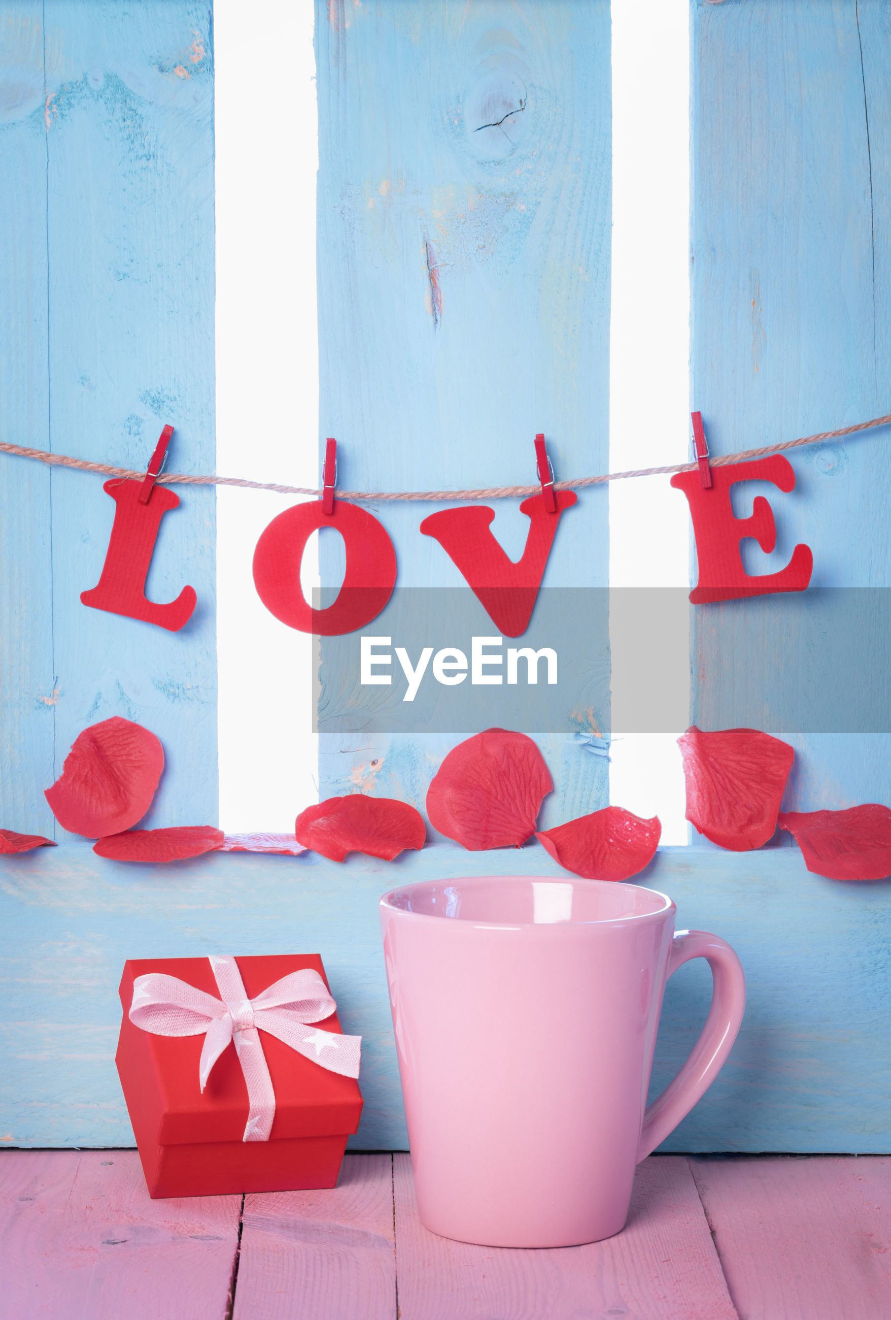 Close-up of love text hanging over petals and mugs