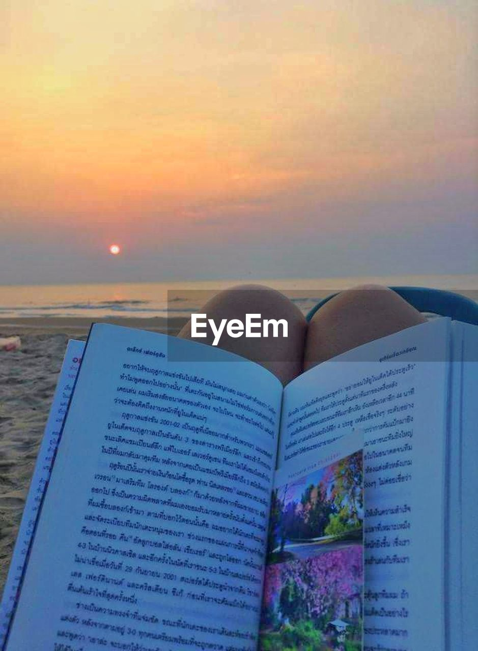 sea, water, beach, text, sunset, sky, book, horizon over water, scenics, nature, close-up, outdoors, beauty in nature, no people, day