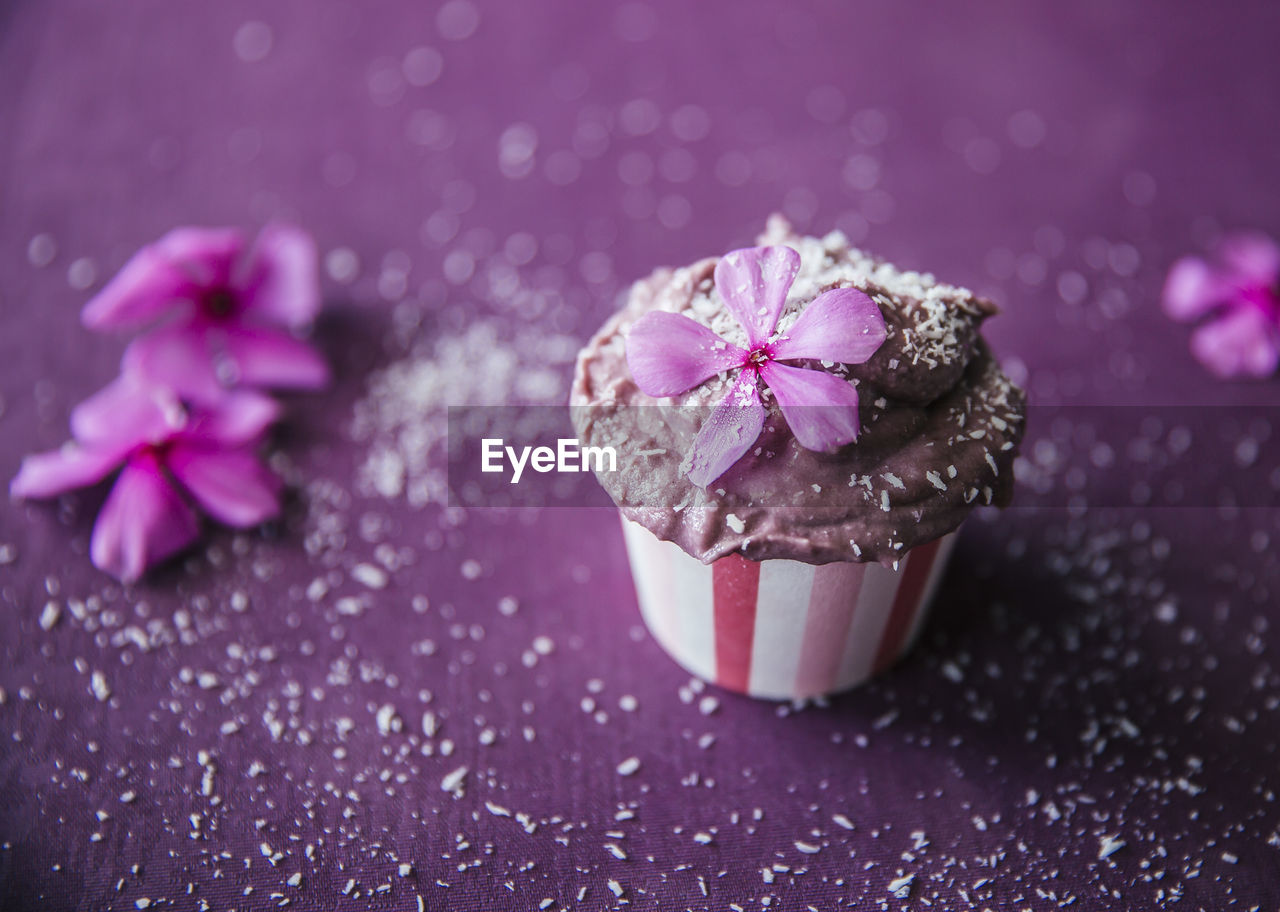 sweet food, freshness, sweet, dessert, temptation, cake, food and drink, food, indulgence, pink color, close-up, unhealthy eating, cupcake, baked, ready-to-eat, no people, indoors, still life, table, flowering plant, purple, icing, baked pastry item, cupcake holder, powdered sugar