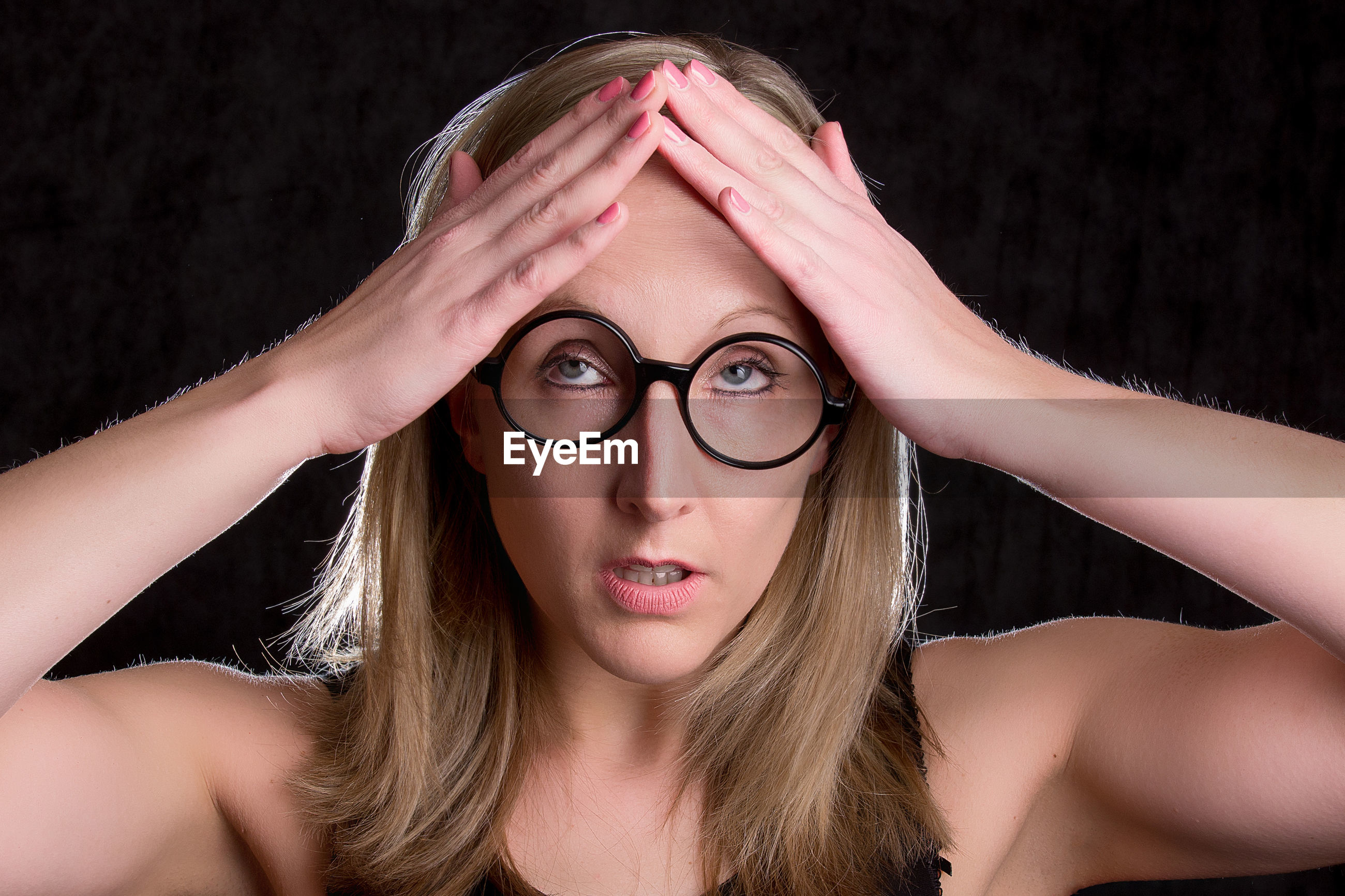 Woman in eyeglasses with headache against black background