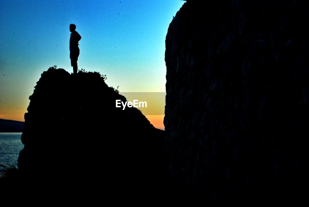 silhouette, sunset, real people, rock - object, sky, full length, one person, men, leisure activity, nature, clear sky, scenics, standing, lifestyles, beauty in nature, cliff, outdoors, women, water, day, people