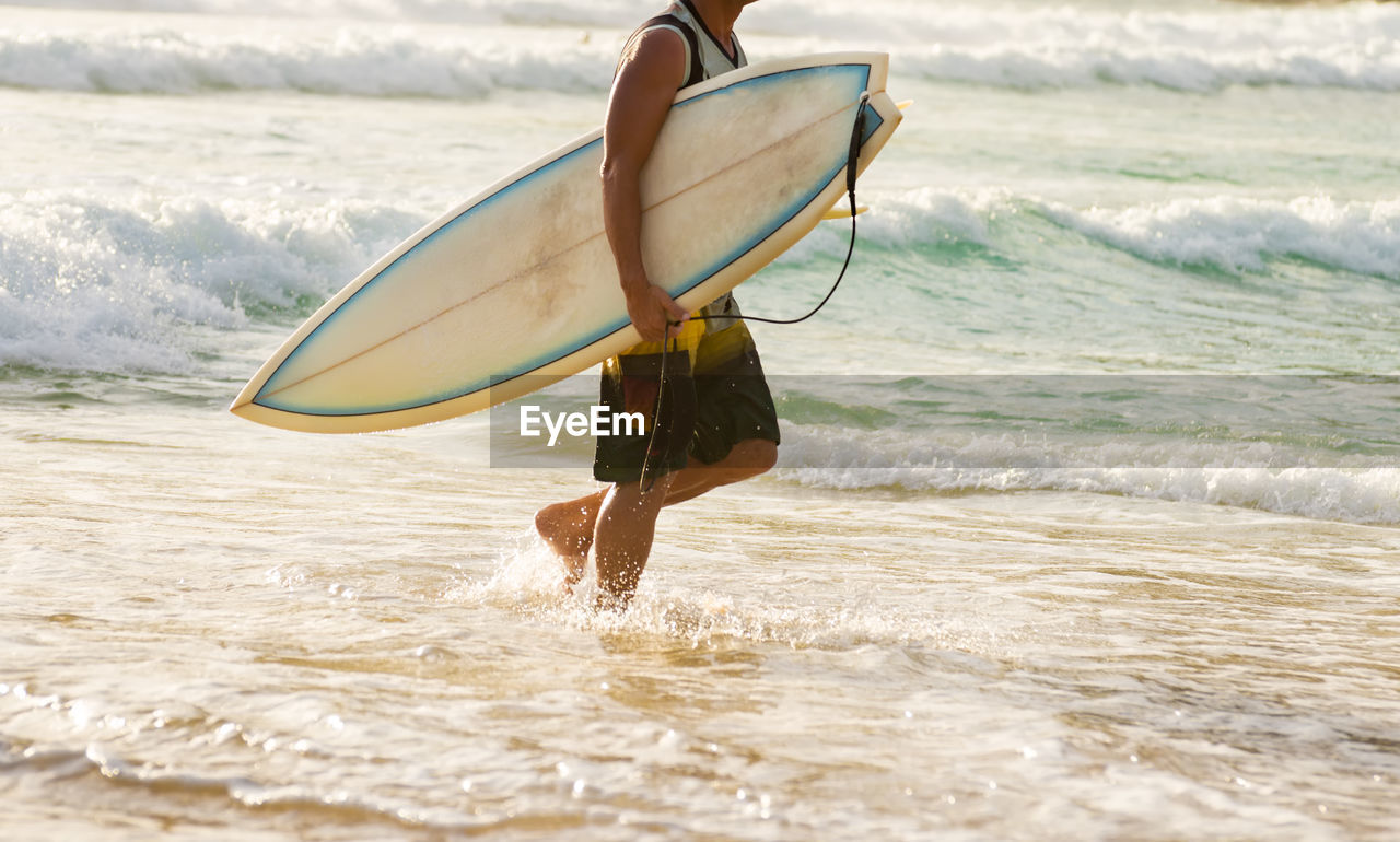 Side view of man with surfboard walking at beach