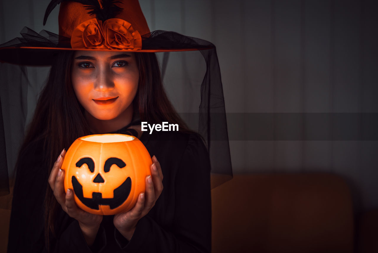 halloween, jack o' lantern, pumpkin, celebration, indoors, front view, portrait, orange color, real people, one person, women, illuminated, focus on foreground, face, food and drink, looking at camera, art and craft, witch