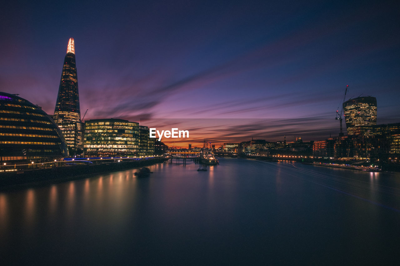Shard london bridge by thames river in city at dusk