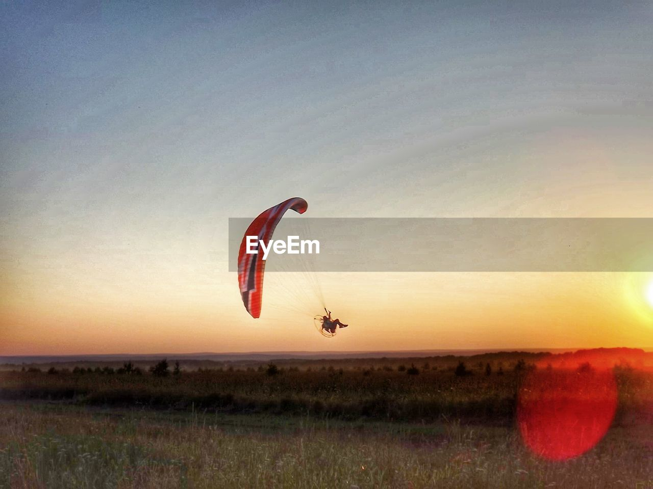 Man flying powered parachute over grassy field against clear sky during sunset