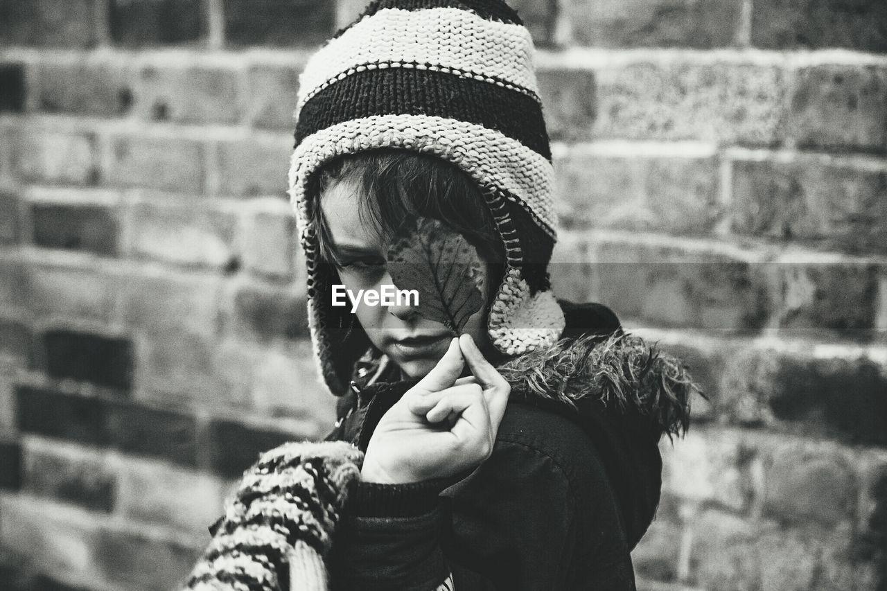 Boy In Warm Clothing Holding Leaf Against Brick Wall